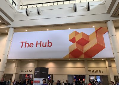 Photograph taken at a conference, with a large banner of The Hub in view