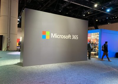 Photograph taken at a conference of a large Microsoft 365 banner on a wall