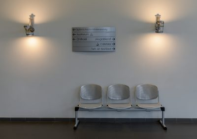 Picture of the waiting room at Gemeente Buggenhout, showing a bench with three seats and a signpost on the wall above it