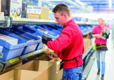 Photograph of an employee working at ICT Logistics, wearing a red shirt and standing in front of blue boxes