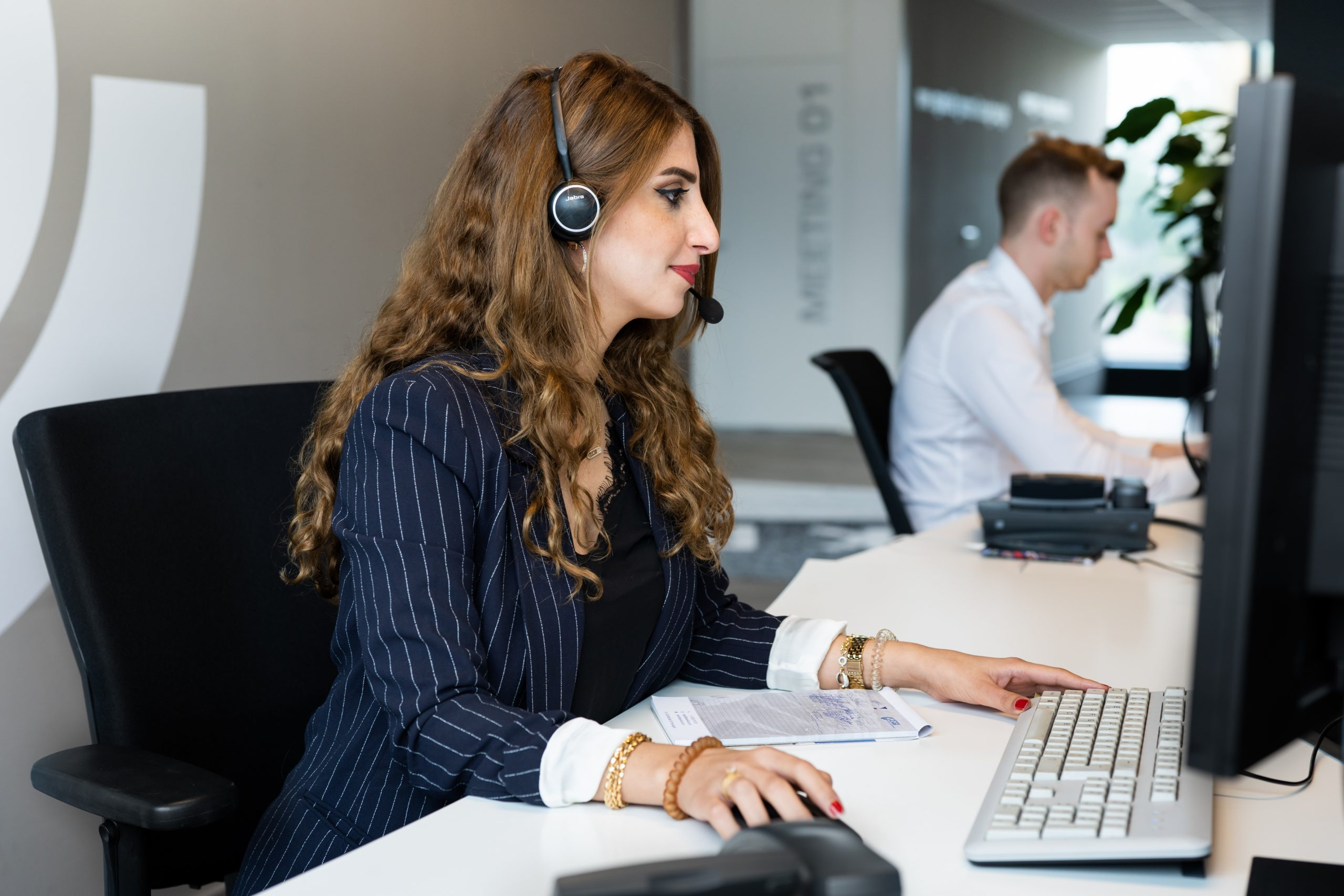 Photograph of an employee at Network4Cars sitting behind a computer, wearing a headset and business attire