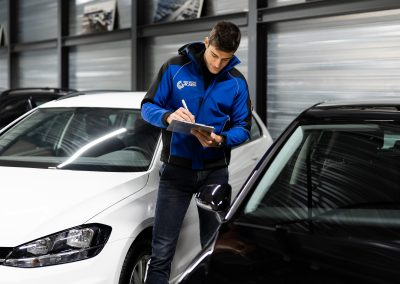 Photograph of an employee of Network4Cars, surrounded by cars and wearing a blue jacket and writing something down on a notepad